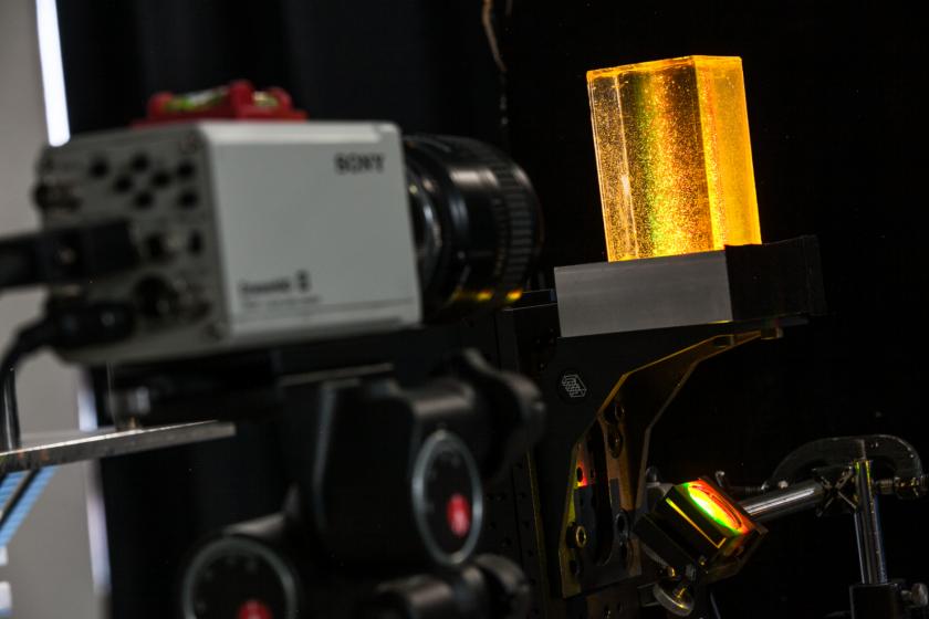 Une caméra pointant vers un bloc de résine incrusté de bulles dans une lumière arc-en-ciel