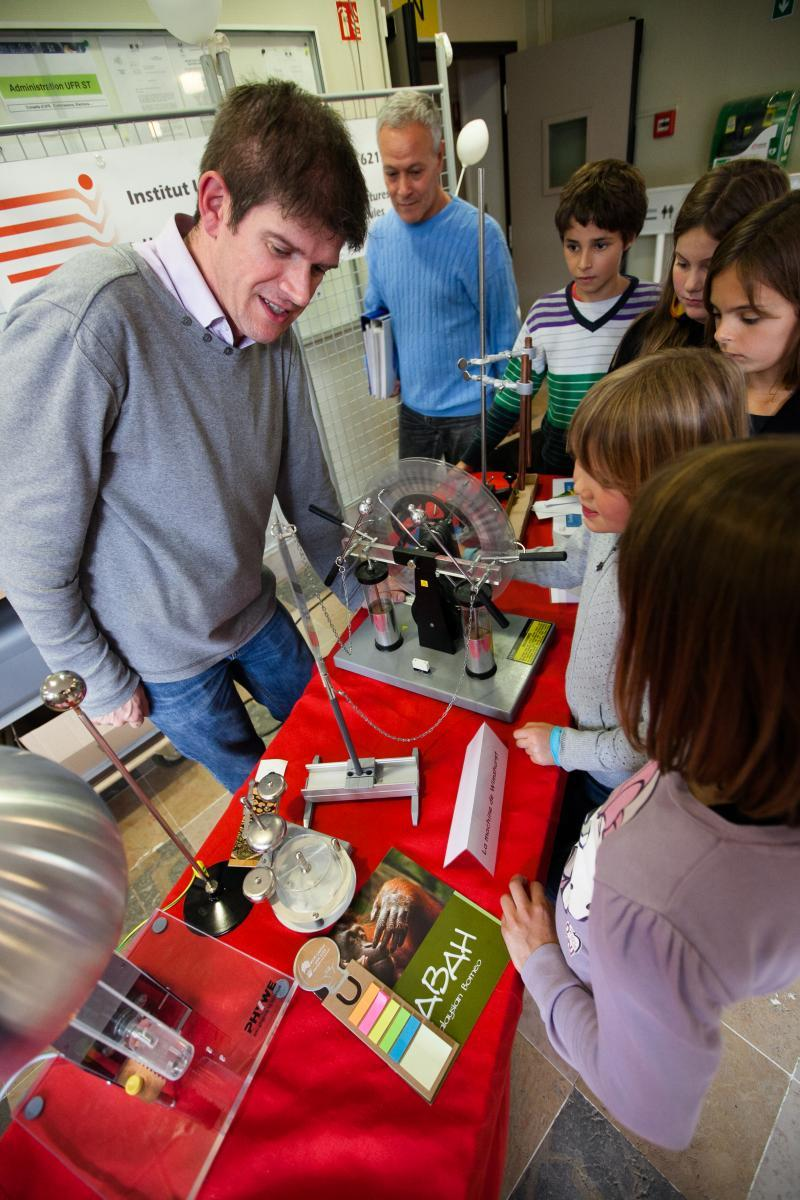 un chercheur montre à plusieurs enfants une expérience sur l'électromagnétisme
