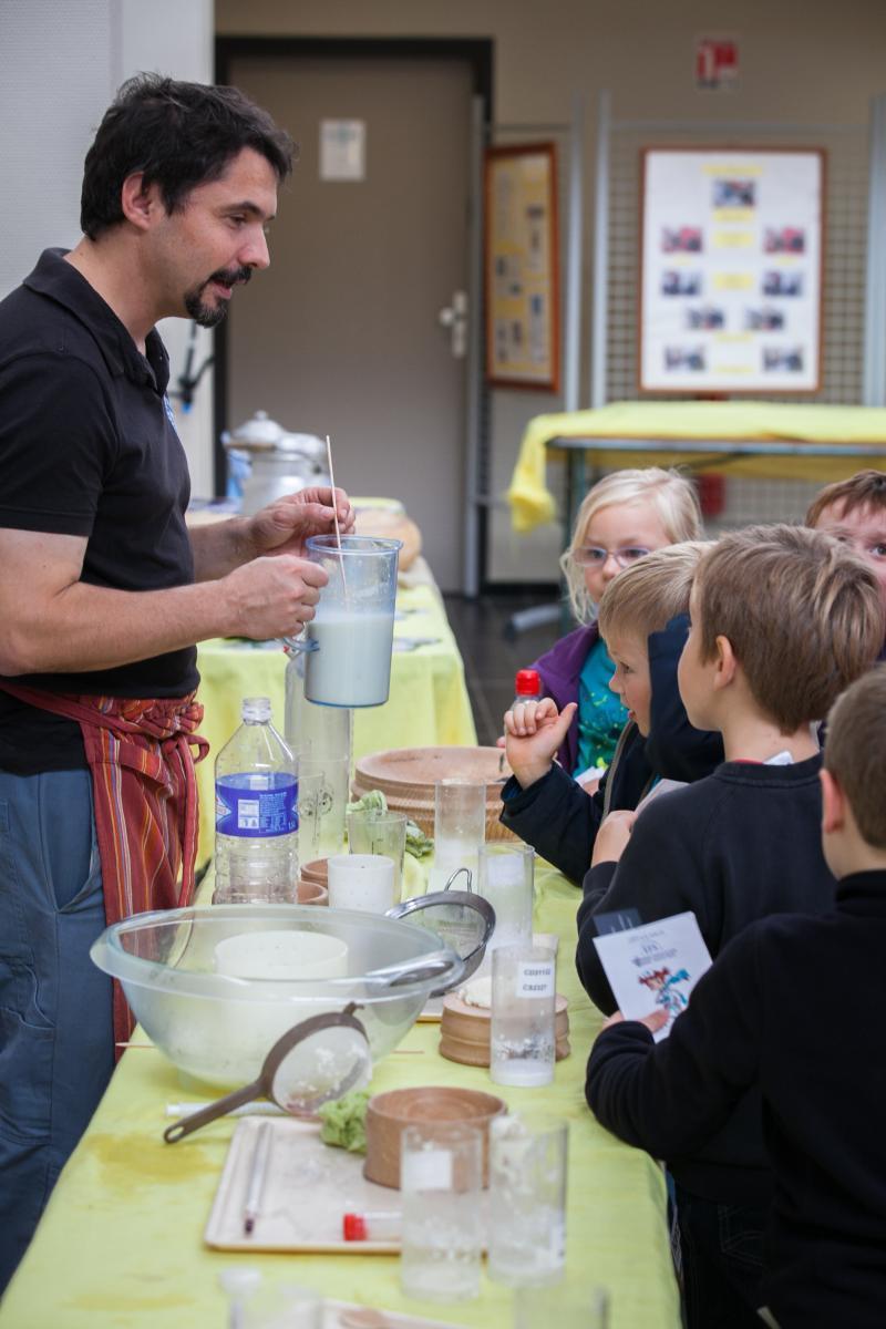 Un homme tient une cruche de lait devant un groupe d'enfants.