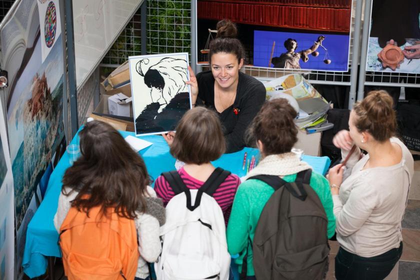 Une jeune femme montre une image à un groupe d'enfants.