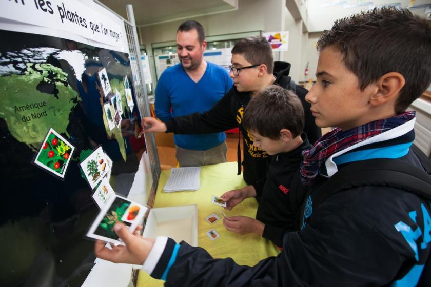 Trois garçons collent des étiquettes sur une mappemonde.
