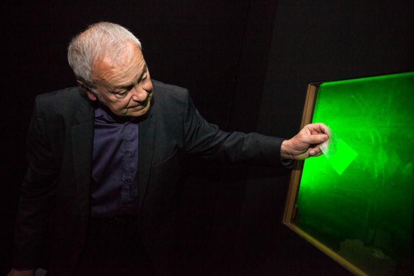 Un homme tient un calque devant un hologramme.