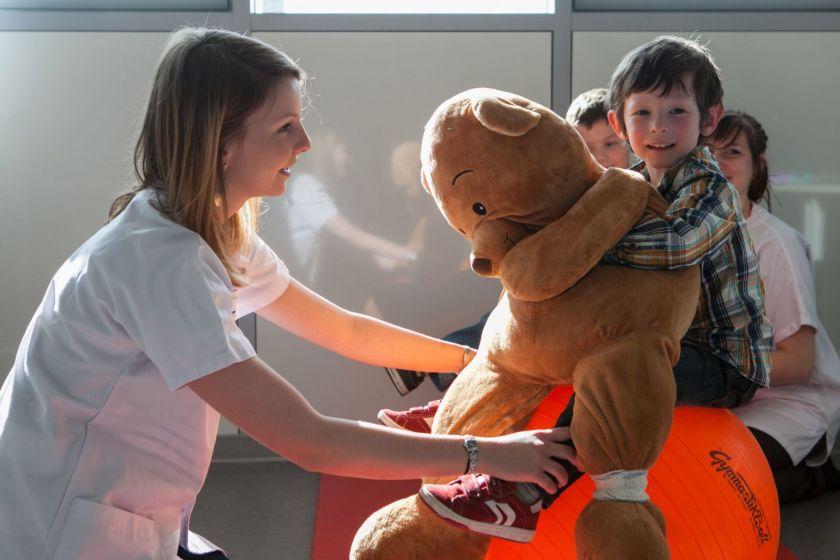 Un petit garçon tient un énorme nounours sur un gros ballon. Une étudiante en blouse souriante lui tient les jambes.