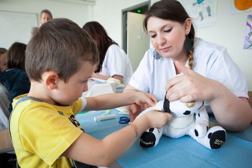Un petit garçon termine un bandage sur son nounours aidé par une étudiante infirmière.