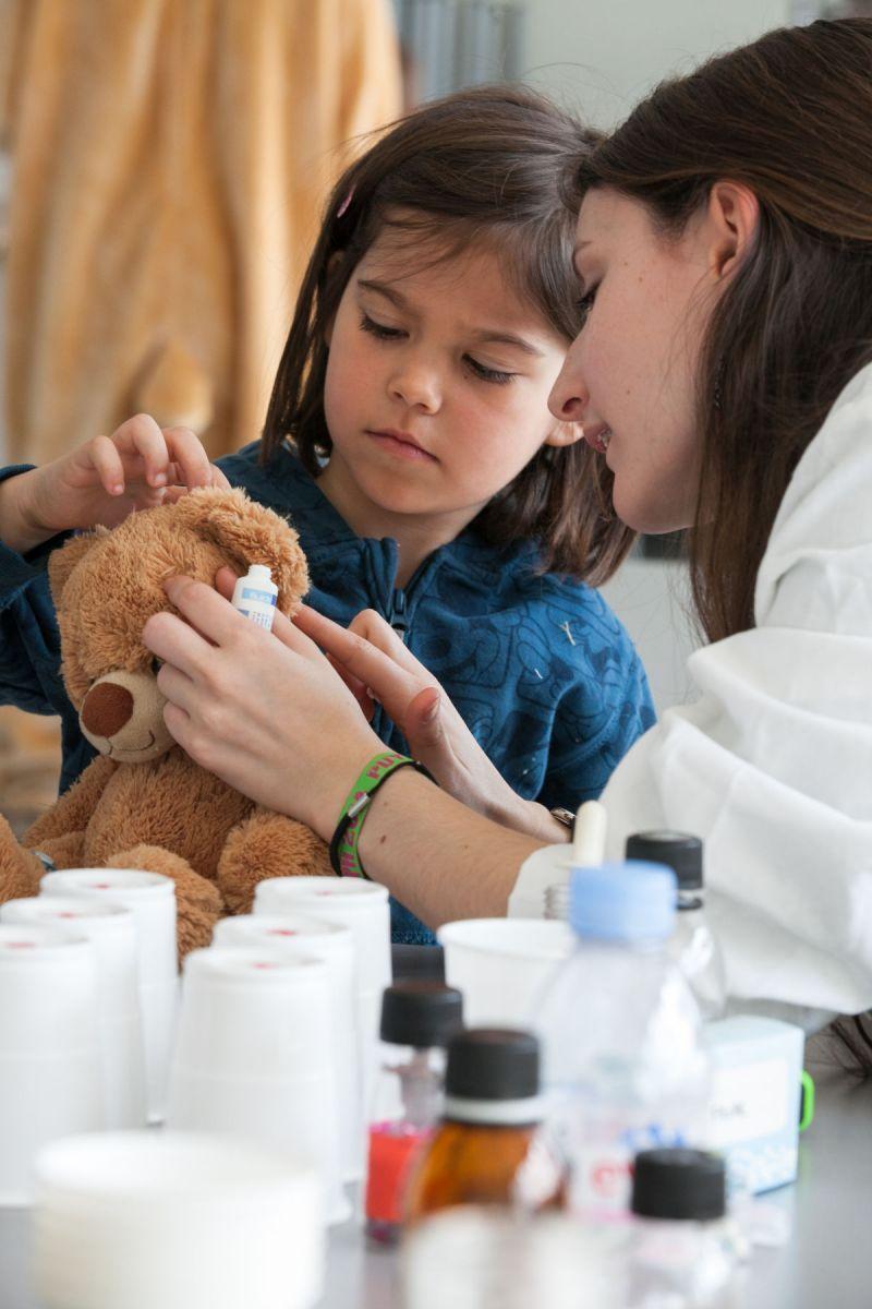 Une petite fille examine les oreilles de son nounours malade en compagnie d'une étudiante en pharmacie.