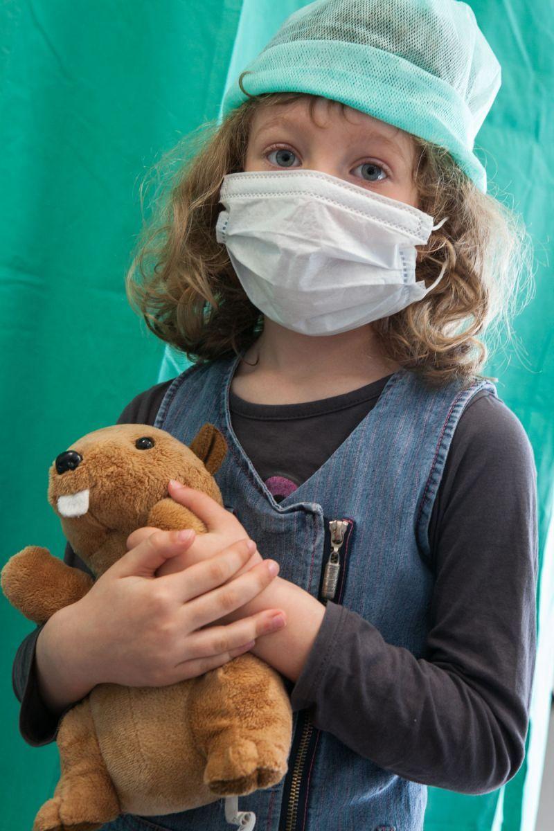 Une petite fille tient son nounours. Elle porte un masque et une charlotte avant d'entrer au bloc opératoire.