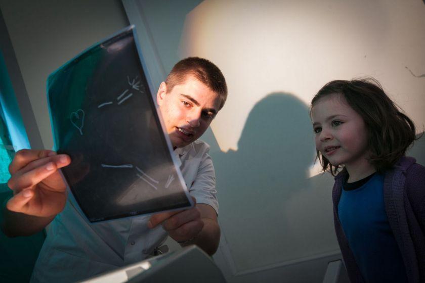 Un jeune homme en blouse montre une fausse radio à une petite fille.