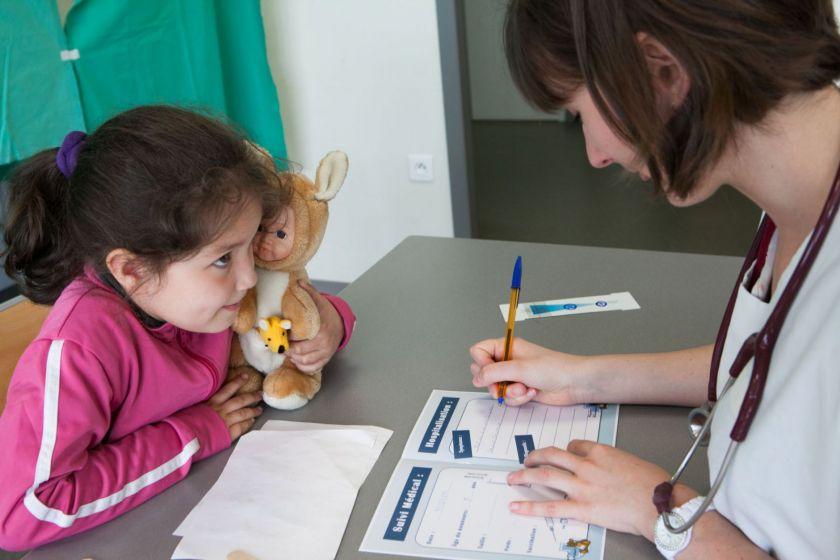 Une petite fille tient son nounorus assise à une table en face d'une jeune femme équipée d'un stétoscope qui remplit un carnet.