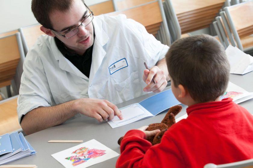 Un étudiant en médecine, crayon en main, interroge un petit garçon.