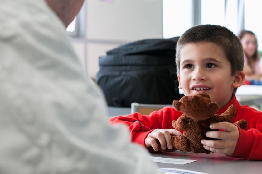 Un petit garçon souriant assis à une table présente son nounours à un adulte de dos.
