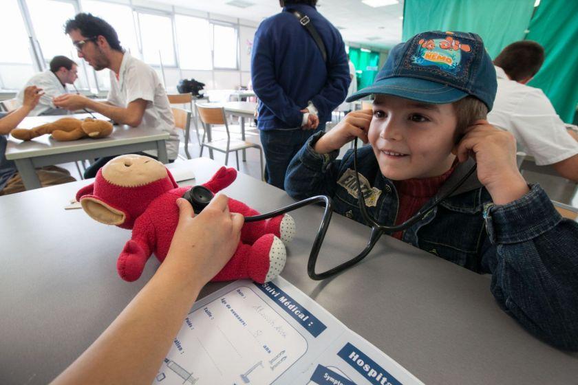 Un petit garçon à casquette écoute le coeur de son nounours au stéthoscope