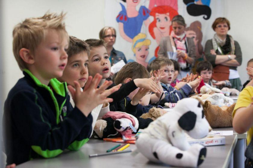 Plusieurs enfants assis à table et attentifs se frottent les mains.