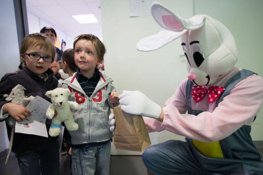 Un homme déguisé en lapin tend un sac en papier à un enfant. Une série d'enfants sont placés en rang.