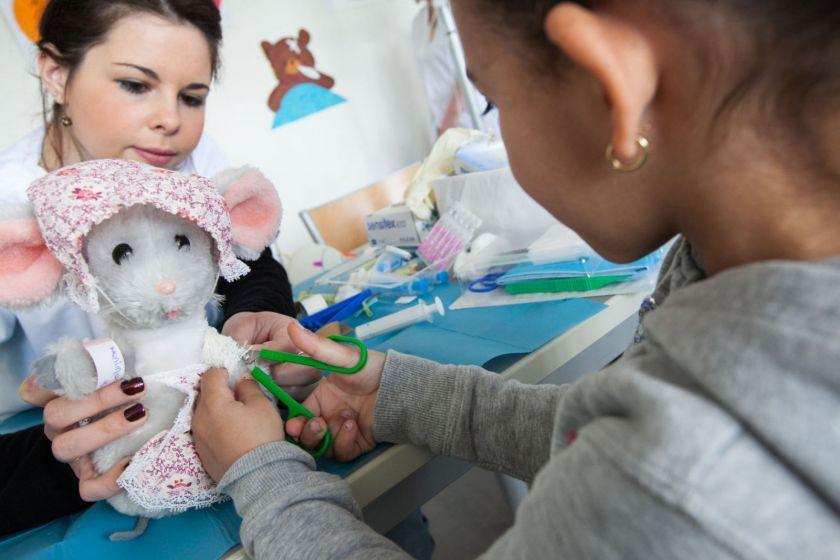 Une petite fille coupe un bandge sur une souris en peluche tenue par une étudiante.
