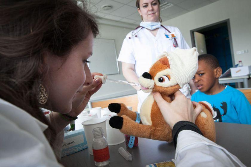 Une jeune fille en blouse donne des gouttes à un nounours bambi sous l'oeil inquiet d'un petit garçon.