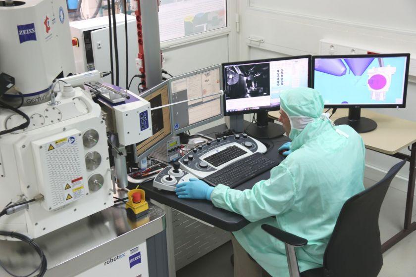 Jean-Yves Rauch devant des écrans d'ordinateur et des appareils de microfabrication.