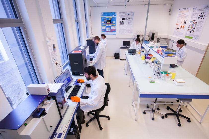 Un laboratoire avec deux hommes et trois femmes en bloise qui travaillent dedans. Plusieurs postes informatiques sont installés et des posters scientifiques sont accrochés aux murs.
