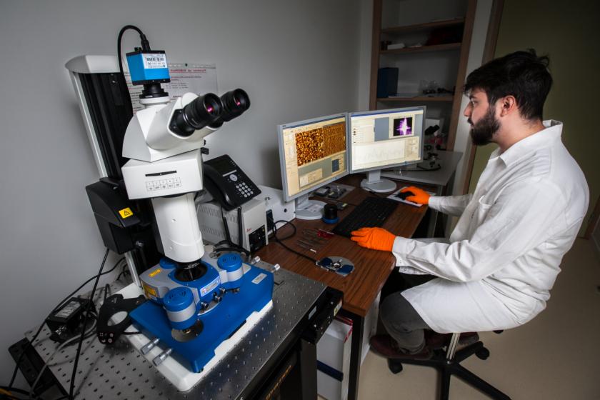 Un jeune homme barbu en blouse blanche et gants orange devant un ordinateur où sont affichées des images de microscopie. A côté de lui au premier plan, un microscope à force atomique.