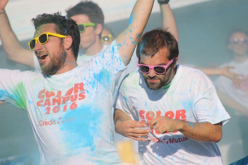 Deux étudiants avec des tee shirts blancs constellés de poudre colorée et des lunettes de couleur font des gestes enthousiastes.