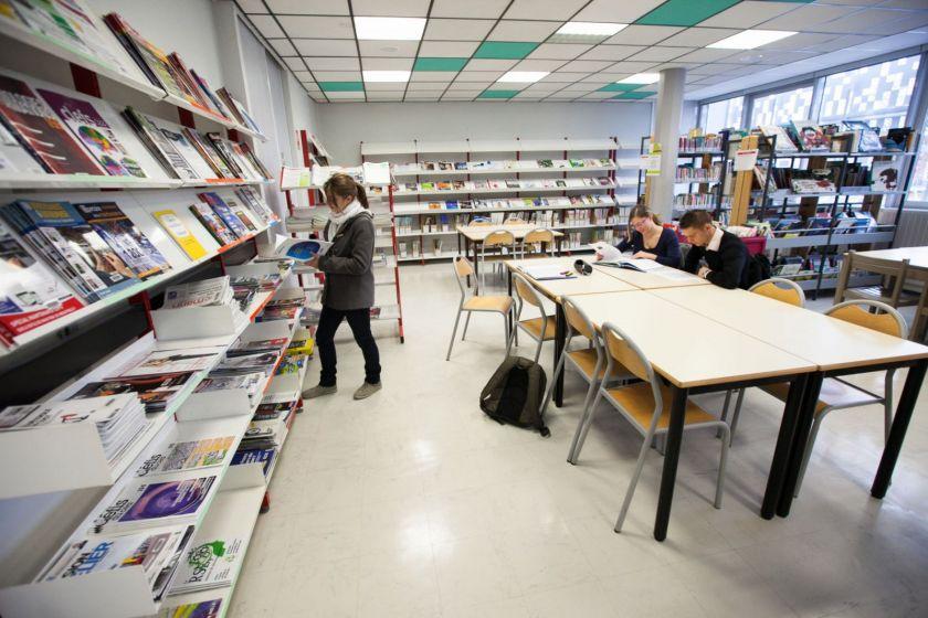 Trois étudiants dans une bibliothèque.