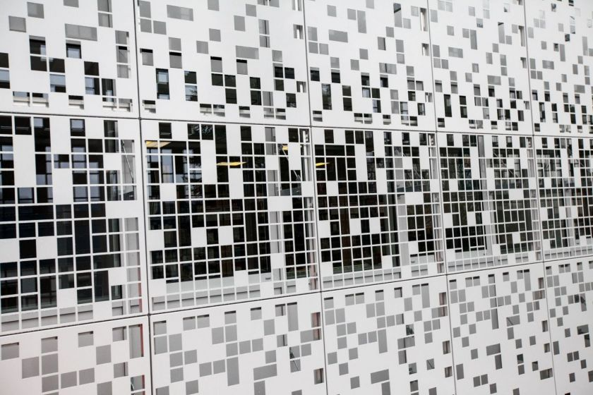 Résille métallique sur une façade de bâtiment.