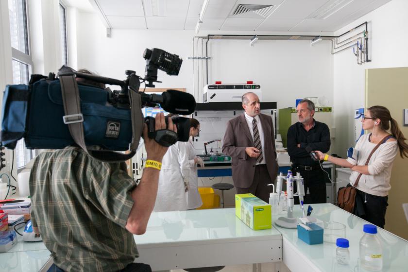 Dans une salle de laboratoire, un caméraman et une journaliste radiophionique tenant son micro en compagnie de Frédéric Chérioux et Hervé Mayotte.