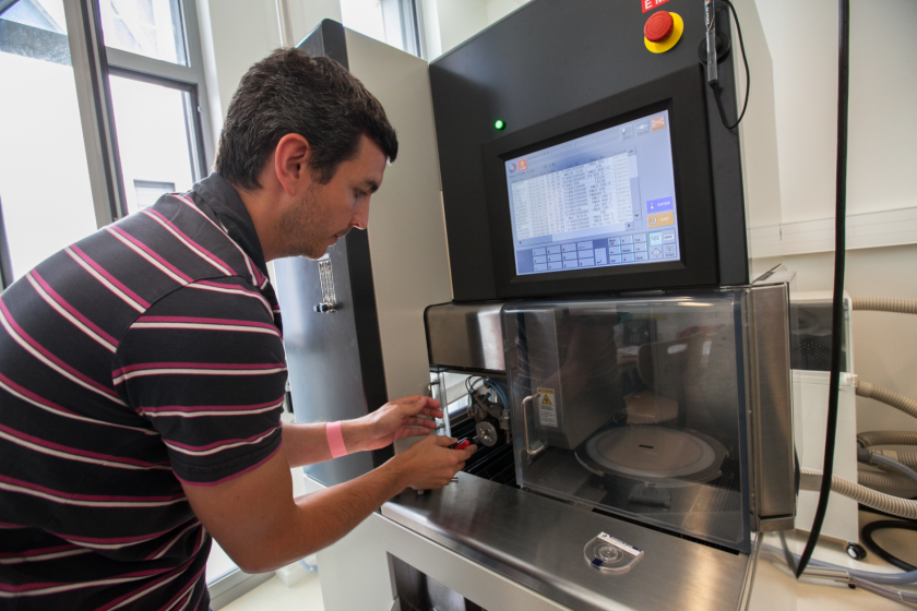 Un homme face à une machine dotée d'une scie de précision.