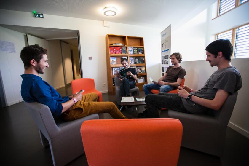 Quatre jeunes hommes aussi dans des fauteuils dans un espace convivialité. Derrière, une étagère avec des revues scientifiques.