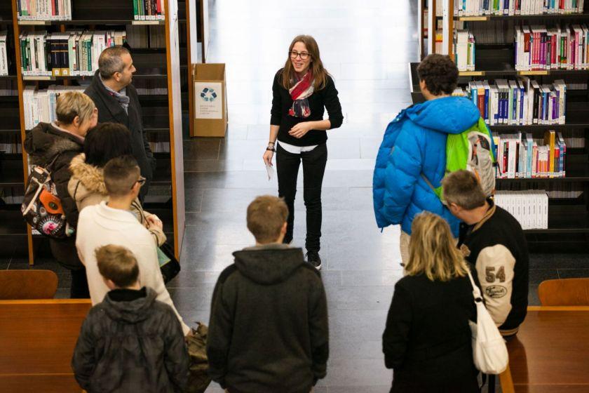 Une étudiante face à un groupe de visiteurs dans une bibliothèque.
