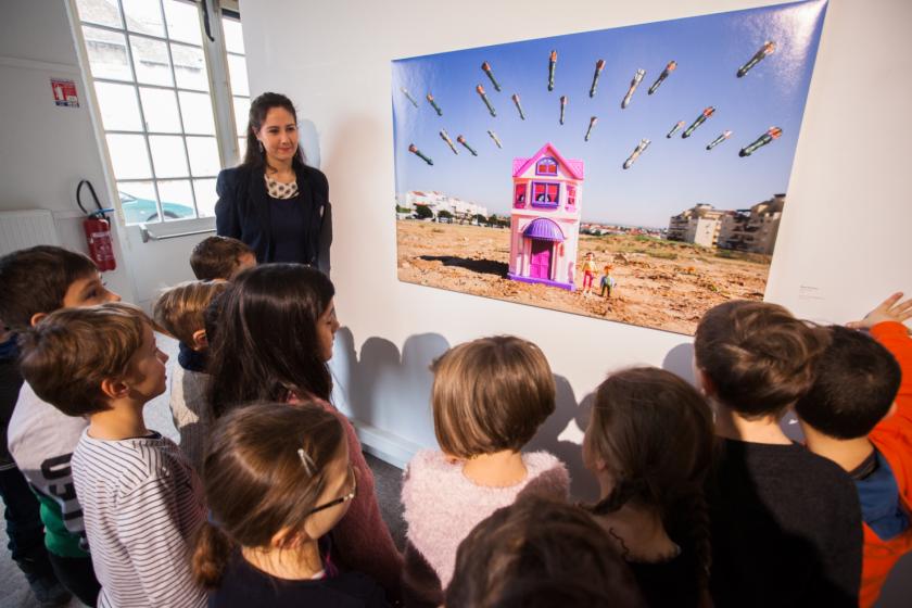Une jeune femme et un groupe d'enfants devant une photo de Brian Mc Carty