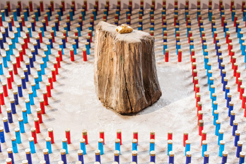 Installation d'Antonin Lagarde, avec un char doré placé sur un billot de bois autour duquel sont alignés des rangs de cartouches.