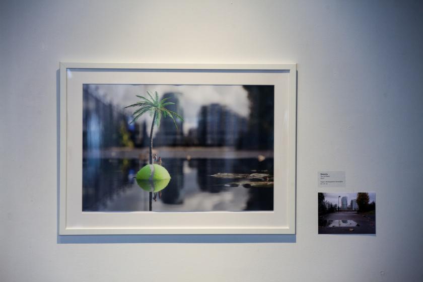 Deux photos de l'artiste Slinkachu exposées sur un mur. On y voit une fausse île faite d'une balle de tennis avec un palmier et des personnages miniatures.