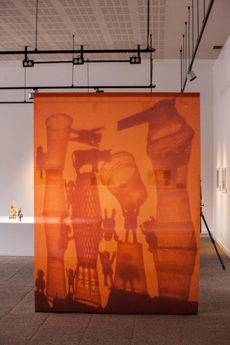 Une toile sur laquelle est imprimée une photo d'ombres de jouets et de gobelets en plastique. Ouvre de Isabelle Bralet.