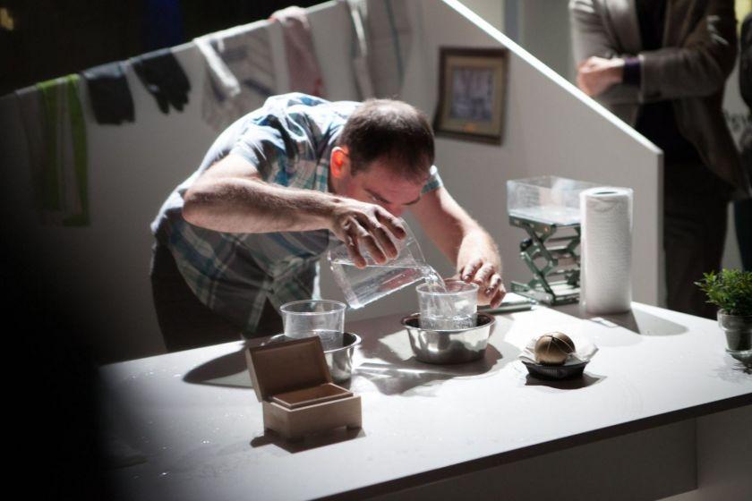 Un homme en train de verser des liquides dans différents récipients.