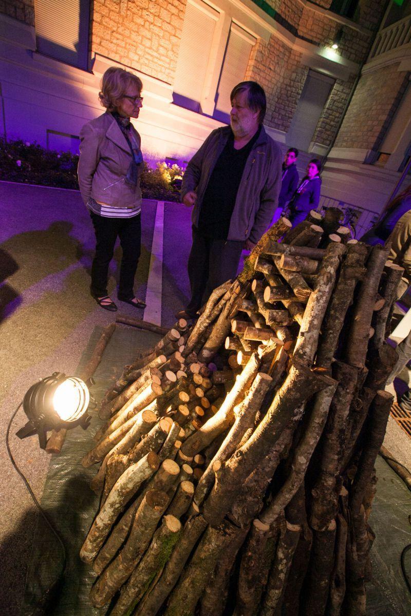 Deux personnes discutent devant un tas de bois.
