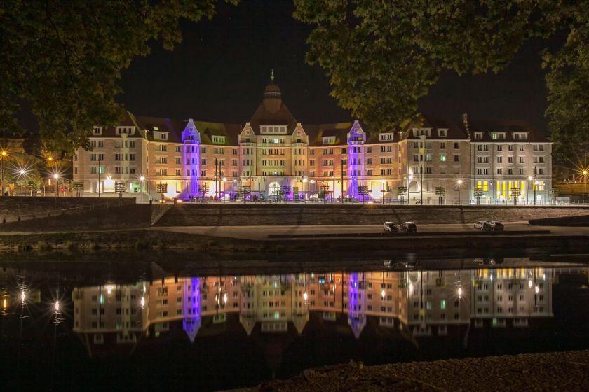 La cité universitaire Canot, vue de l'autre rive, éclairée, avec son reflet dans l'eau.