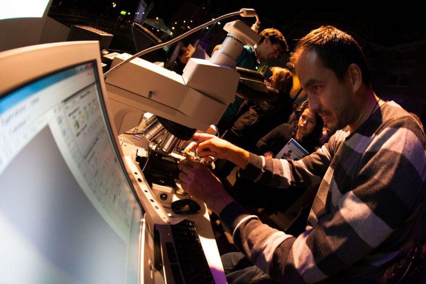 Un homme place un matériau sous un microscope. Au premier plan un écran d'ordinateur et du public en arrière plan.