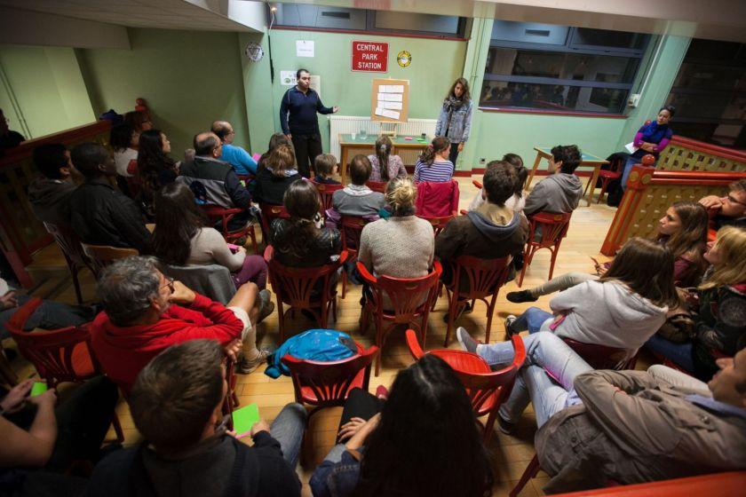 Deux personnes debout parlent devant un public.