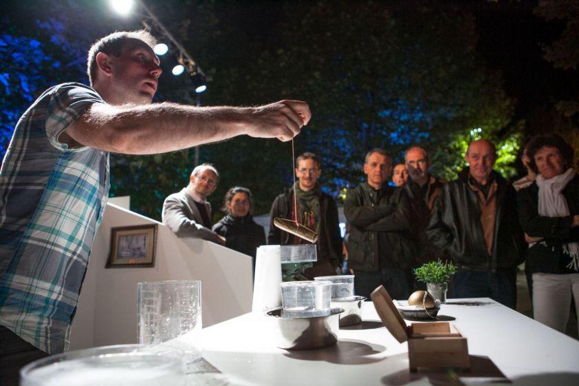 Guillaume Kuntz tient un objet au bout d'une ficelle qu'il va plonger dans l'eau et donne des explications au public.