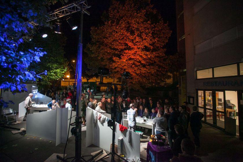 Une foule de visiteurs rassemblé devant des stands. Eclairages colorés dans les arbres.