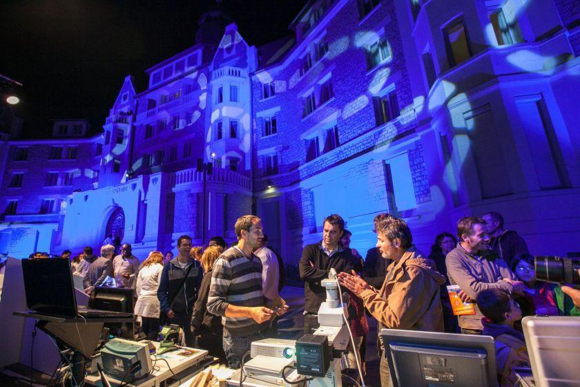Des gens groupés autour des stands devant le bâtiment Canot éclairé avec projection d'images.