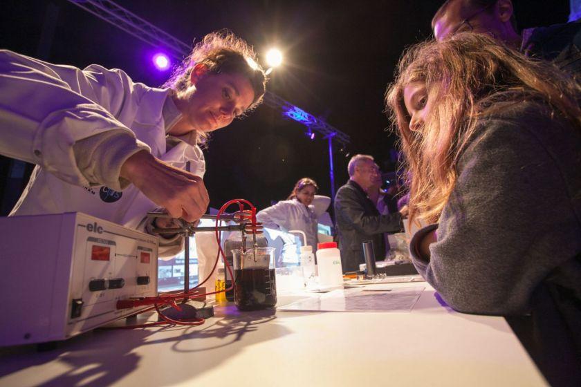 Une femme en blouse dispose une plaque de métal et deux électrodes dans un récipient rempli de liquide. Une jeune fille regarde.