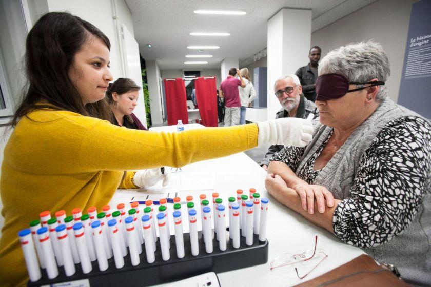 Une étudiante fait renifler un échantillon à une dame aux cheveux blancs les yeux bandés.