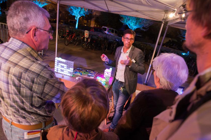 Benoit Piranda devant un stand où sont posées des briques lumineuses parle à du public de dos.