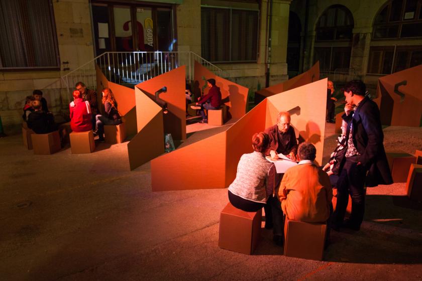 Des gens assis sur des meubles en carton dans une lumière rouge.