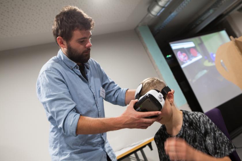 Un jeune homme place un casque de réalité virtuelle sur la tête d'un jeune garçon.
