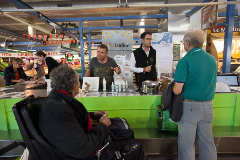 Un stand tenu par des chercheurs au marché avec deux visiteurs devant dont un en fauteuil roulant.