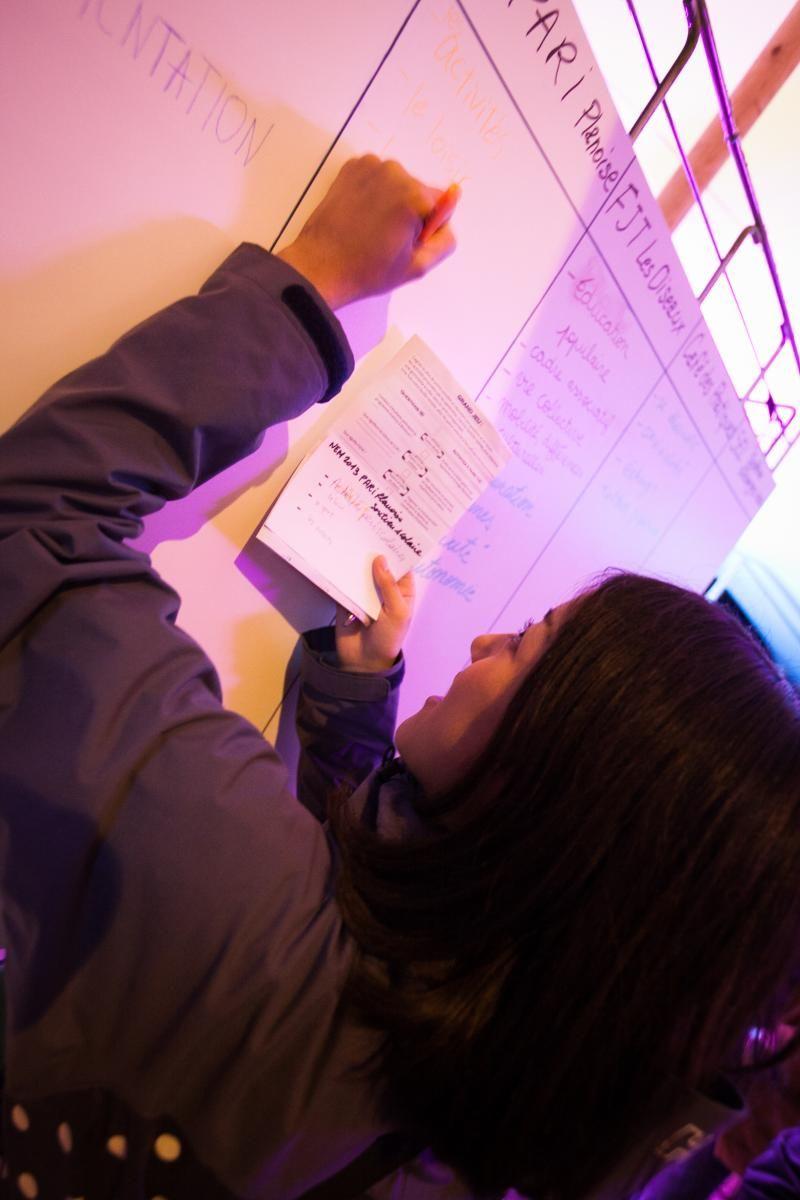 jeune fille en train d'écrire sur un tableau