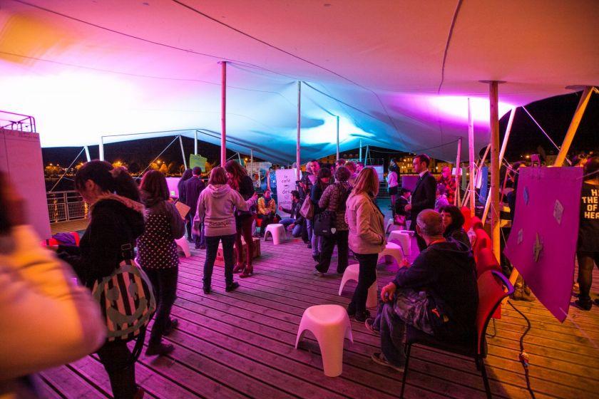 des visiteurs et de nombreux stands dans une ambiance d'éclairages colorés