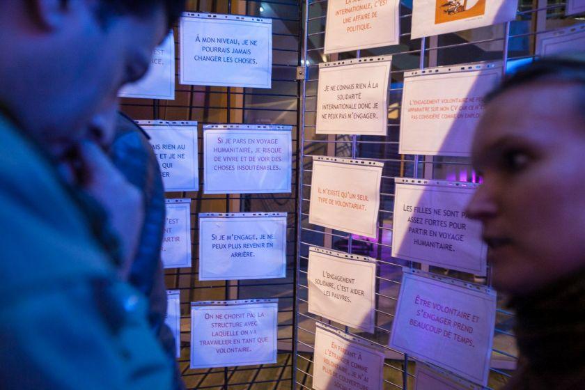 Deux personnes discutent devant des panneaux où sont placardées de nombreuses idées reçues.